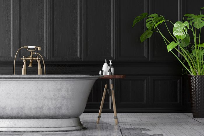 This art deco inspired bath makes a statement against the contemporary black paneling in this moody bathroom