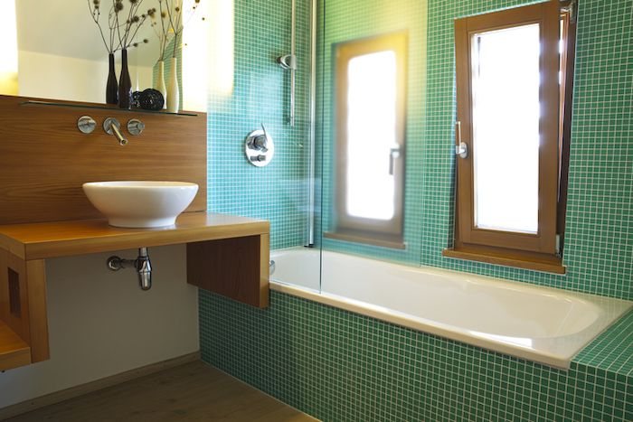 The green tiles, applied to walls and the bath surround create the focal point for this bathroom.